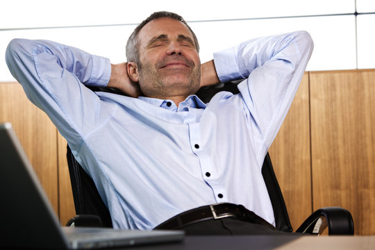 Smiling manager relaxing in office chair.