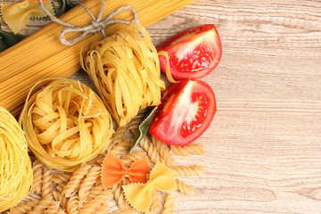different pasta and spices on wooden background