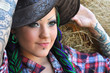 young tattooed stylish woman with dreadlocks in cowgirl style