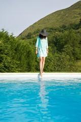 woman test water on swimming pool border