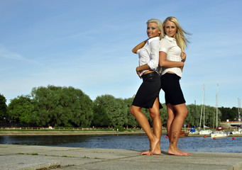 Two barefoot girls on river bank
