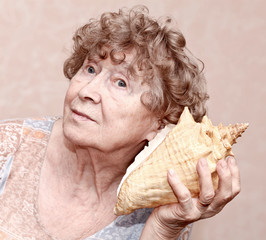 Smiling great grandmother listening to a seashell