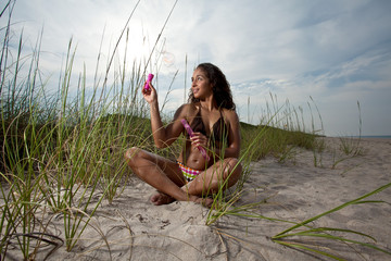 Young Brunette Woman at the beach playing with bubbles