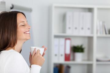 entspannte frau mit kaffeetasse im büro