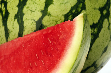 Water melon slice in front of whole melon.