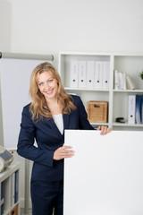 lächelnde frau im büro zeigt eine weiße tafel