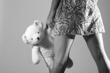 Legs of girl holding teddy bear in hand