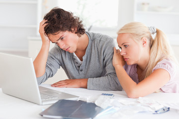 Upset couple with bills and a notebook