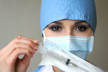 Portrait of a young female doctor holding a syringe