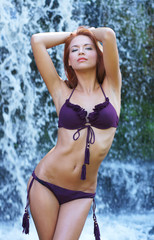 A young redhead woman in purple lingerie standing in a waterfall