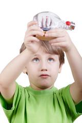 Boy in t-shirt looks at miniature model of tallship in bottle