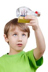 Boy in green t-shirt looks at model of tallship in bottle