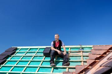 dachdecker sitzt auf dem dach
