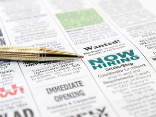 Pen on the newspaper career opportunity ad.