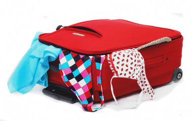 red luggage bag of which looks out summer clothes