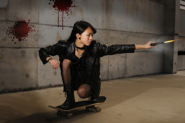 Young asian gang member shooting a gun while riding a skateboard