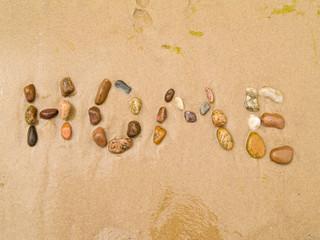 home written in pebbles on sea shore concept