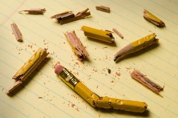 Broken pencil fragments on yellow paper