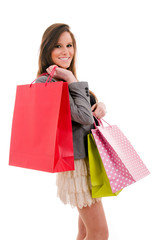 Smiling beautiful young woman with shopping bags, isolated on wh