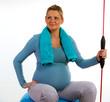 schwangere sportliche Frau auf gymnastikball mit sportgerät