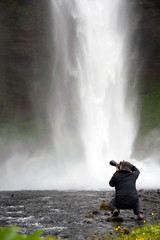 photographer taking picture of Seljalandsfoss waterfall, Iceland