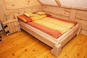 Wooden rustic bed in country cottage bedroom.
