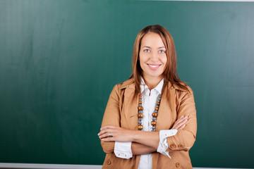 lächelnde lehrerin mit verschränkten armen
