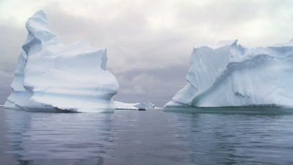Wall Mural - two huge icebergs and a small boat in antarctica