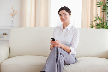 Cute Woman sitting on a sofa with a phone