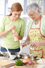Women having fun in kitchen smiling