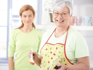Cheerful senior mother cooking in kitchen