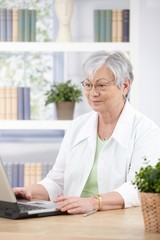 Mature woman working at home on laptop