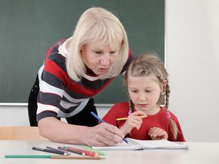 Ältere Lehrerin hilft Schülerin beim Unterricht