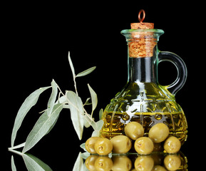 olive oil in jar and olives on black background
