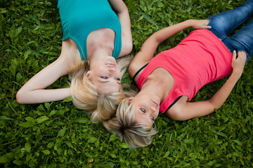 Two girls lie together on the grass and enjoy