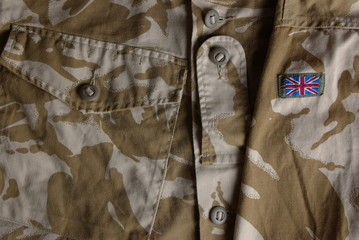 British army combat uniform jacket and a flag
