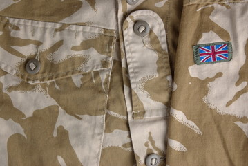 British army desert uniform jacket and a flag