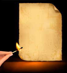 Background with old paper and hand holding a burning match