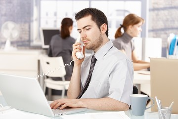 Young office worker using laptop talking on phone