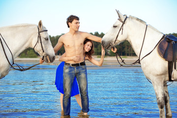 Young couple in the sea with horses