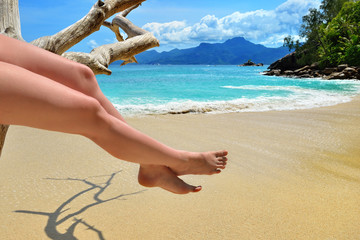 Sand beach, azure sea and woman's legs