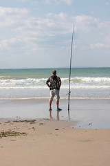 fisherman casting until the fish on a sandy beach