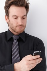 Portrait of young businessman with mobile