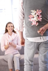 Young man bringing flowers to woman