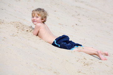 Boy laying in the sand at the base of a sand dune