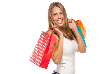 Side view of young happy female holding shopping bags