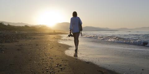 Mujer paseando por la playa con puesta de sol