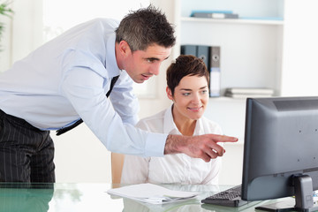 Businessman pointing at something on a screen to his secretary