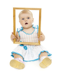 Close-up portrait of little girl looking through a wooden frame