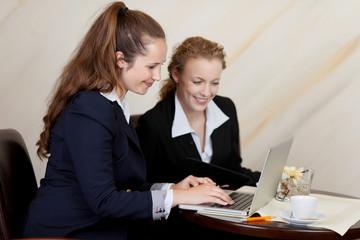 zwei geschäftsfrauen am laptop in der hotellobby